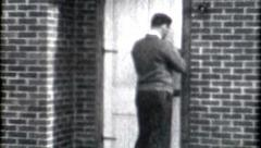Male locking door 1940s black and white security lock safty vintage fashion life Stock Footage