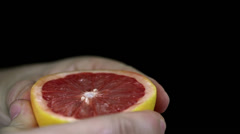 Squeezing a grapefruit which spurts its juices in slow motion Stock Footage