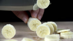 Slicing a banana into thin slices in slow motion Stock Footage