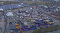 Aerial view of cranes and containers lined up at a busy London port. Stock Footage