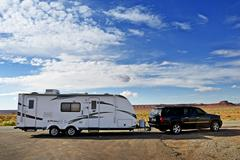 rv trailer journey. travel trailer pulling by SUV - stock photo