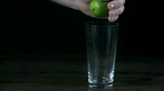 Lime juice pours rapidly into the glass while hand is squezzing the lime Stock Footage