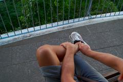 Naked tanned legs of male guy in sports shoes Stock Photos