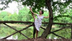 Beautiful ballerina doing exercises in a park Stock Footage