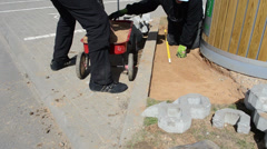 Workers take sand from a small red wheelbarrow strew the ground Stock Footage