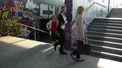 Women walk upstairs from city underground dark passage subway Stock Footage