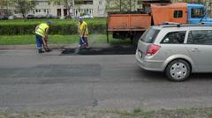 Workers shovel put hot asphalt street road holes street repair Stock Footage