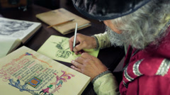 An old medieval scholar writing in calligraphic writing Stock Footage