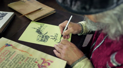 An old medieval scholar subscribing himself in calligraphic writing - stock footage