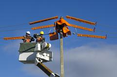 Electrical workers repairing power pole Stock Photos