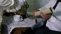 Man gets his cup of tea while checking the geographical map - stock footage