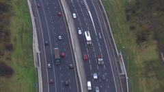 Aerial view of a traffic driving on a motorway through the English countryside. - stock footage