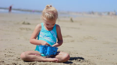 Little Girl playing with sea shells on the beach Stock Footage