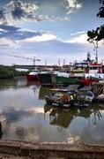 supply boat and fishing boat at jetty - stock photo