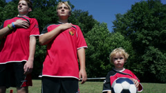 Kids listening to the national anthem in football dress Stock Footage