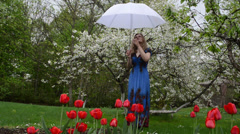 Woman dress umbrella in spring garden tulips blooming trees Stock Footage