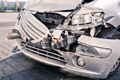 a demolished car after an accident on the street - stock photo