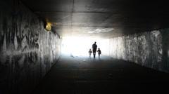 Man with children walk underground dark passage subway Stock Footage
