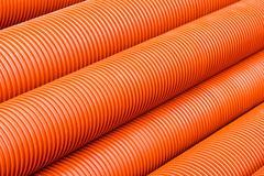 Orange plastic PVC pipes - stock photo