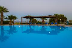 a swimming pool with sun loungers - stock photo