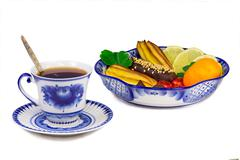 """cup of tea, cakes, sweets, fruit bowl, painted in the style of the """"gzhel"""" - stock photo"""