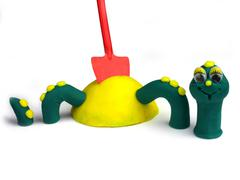 laughing plastiscines green worm in the sandbox, children worm no. 03 - stock photo
