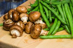 Mushrooms and green beans on a wooden board Stock Photos