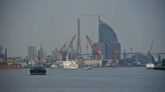 Ships pass by shanghai huangpu river pier,tower cranes on construction site. Stock Footage