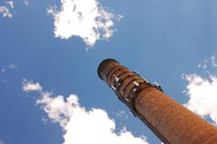 Smoke Stack Rises into Blue Sky - stock photo