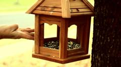 Filling bird feeder Stock Footage