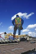 Roofing contractor on the roof repairing Stock Photos