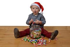Baby with santa hat eat a lot of sweets Stock Photos