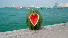Watermelon with heart shaped cut with sea view time lapse loop - stock footage