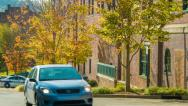 Stock Video Footage of Car Passing Fall Colored Tree-lined Street at Asheville Police Station