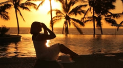Woman sits by tropical resort pool at sunset Stock Footage