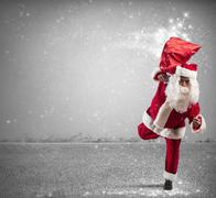 Running santa claus with magic gifts Stock Photos