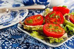 Blue crockery with fresh tomatoes Stock Photos