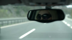 Shot of woman with sunglasses visible in rearview mirror driving towards tunnel - stock footage