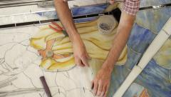 Man fits stained glass piece into window design Stock Footage