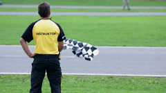 Referee with a chequered flag stands at the side of the go-cart racing track Stock Footage