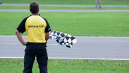 Stock Video Footage of Referee with a chequered flag stands at the side of the go-cart racing track