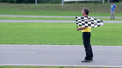 Referee standing firm and signaling to the go-kart competitors Stock Footage