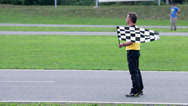 Stock Video Footage of Referee standing firm and signaling to the go-kart competitors