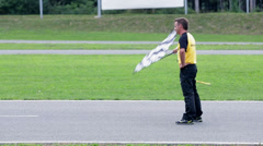 Referee signals the end of the race with checkered flag on a windy day Stock Footage