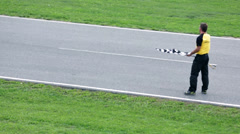 Referee standing on a racing track with racers passing by Stock Footage