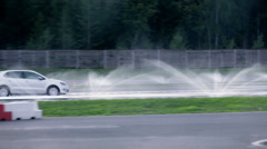 White car going through a safety ride with a lot of water on the road Stock Footage