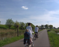 Cyclists along earth rampart fortification near Spaarndam Stock Footage