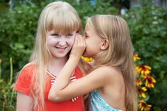 Girls tell each other secrets Stock Photos