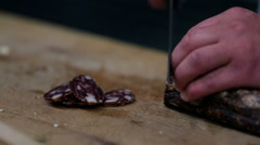 Slicing salami into thin pieces Stock Footage