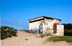 graffiti on wall of old ablution block - stock photo